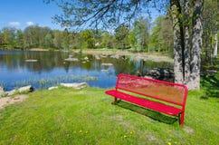 在春天自然风景的红色长凳 库存照片