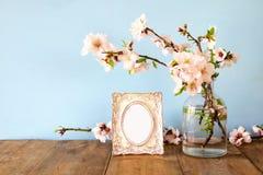 在春天花旁边的葡萄酒空白的照片框架 库存照片