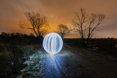 在春天路的发光的球在两棵树之间 图库摄影