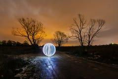 在春天路的发光的球在两棵树之间 免版税库存照片