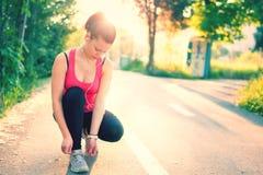 在春天晴朗的日落的妇女连续锻炼 免版税库存图片