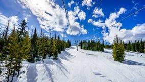 在春天滑雪期间的驾空滑车上在太阳峰顶 库存照片