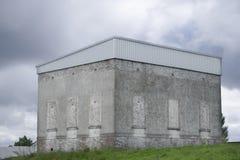 在是一个老能源厂房子的小山的遗弃灰色被困扰的大厦 库存图片