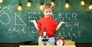在显微镜,时钟附近哄骗男孩在教室,在背景的黑板 第一前迷茫与学习,学会 免版税库存照片