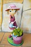 在显示一把愉快的斗眼的女孩喷壶有绿色植物的一个桶黄色的五颜六色的钢做的微笑的木偶 免版税库存照片