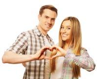 在显示与他们的手指的爱的愉快的夫妇心脏 库存照片