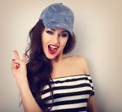 在显示与o的蓝色帽子的疯狂的年轻女性模型岩石姿态 库存照片