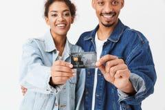 在显示信用卡的牛仔布衬衣的微笑的非洲夫妇 图库摄影