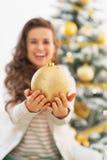 在显示圣诞节球的少妇的特写镜头 免版税库存照片