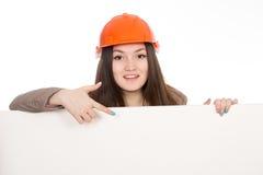 在显示在一副空白的横幅的盔甲的女孩建造者一个手指 免版税库存照片