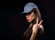 在显示在d的蓝色帽子的年轻性感的女性模型胜利姿态 免版税库存图片
