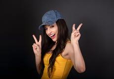 在显示在gre的蓝色帽子的年轻愉快的女性模型岩石姿态 库存照片