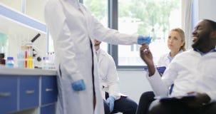 在显示它的试管的非裔美国人的科学家妇女研究化学制品对研究员与队谈论实验  股票录像