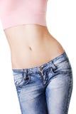 在显示平的腹部的健身妇女的特写镜头 免版税库存照片