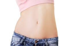 在显示平的腹部的健身妇女的特写镜头 免版税库存图片