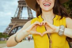 在显示心形的手的愉快的旅行家妇女的特写镜头 库存照片