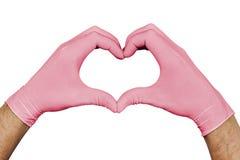 在显示心脏标志的桃红色医疗手套的手隔绝在白色背景 库存照片