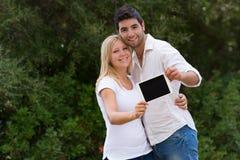 在显示数字式片剂的焦点外面的年轻夫妇在照相机 库存照片