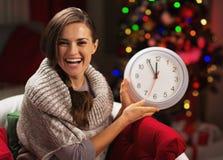 在显示时钟的圣诞树附近的微笑的少妇 免版税库存图片