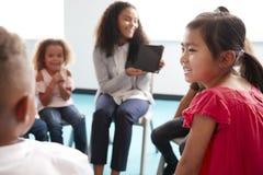 在显示片剂计算机的肩膀观点的微笑的年轻女性学校老师对幼儿学校孩子,坐在圈子 库存图片