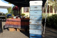 在显示的蓝色蜂箱箱子在蜂蜜摊在农夫市场上 免版税库存照片