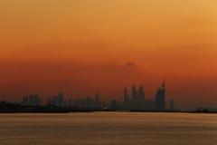 在显示美妙的日落天空的黄昏的迪拜地平线 图库摄影