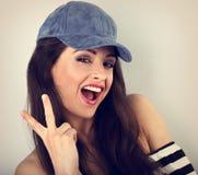 在显示胜利gestu的蓝色帽子的年轻疯狂的愉快的女性模型 免版税库存照片