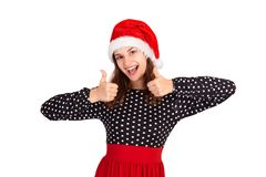 在显示赞许和被投入的手的礼服的少妇模型看照相机 情感女孩在圣诞老人圣诞节帽子isola 库存图片