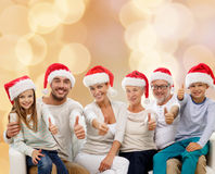 在显示赞许的圣诞老人帽子的愉快的家庭 免版税图库摄影