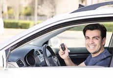 在显示钥匙的汽车的司机 免版税库存照片