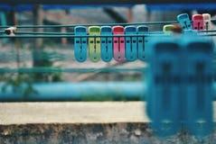 在晒衣绳的多彩多姿的晒衣夹 免版税库存照片