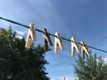 在晒衣绳的晒衣夹反对一明亮的天空蔚蓝 免版税图库摄影