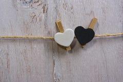 在晒衣绳的两可爱的白色和黑心脏 免版税图库摄影