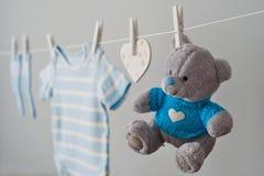 在晒衣绳的蓝色婴儿衣裳 免版税库存照片