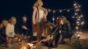在晚上使野餐,朋友在火的烘烤香肠公司靠岸在含沙海岸 影视素材