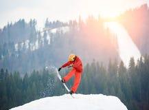 在晚上供以人员跳跃在多雪的小山的上面的挡雪板与雪板的在日落 库存照片