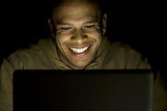 在晚上供以人员后微笑对他的膝上型计算机 库存照片