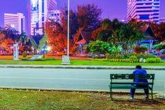 在晚上供以人员坐一条长凳在Lumphini公园 免版税库存图片