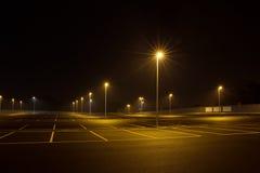 在晚上倒空室外停车场发光与街灯 免版税库存图片