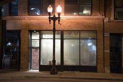 在晚上倒空被放弃的都市城市店面 库存图片
