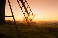 在晚上光的老木风车 库存照片