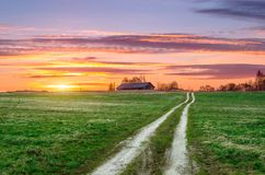 在晚上夏天日落期间,农村风景,在领域的一条路上升到与一个常设谷仓的小山 免版税图库摄影