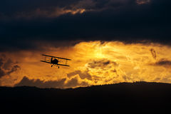 在晚上天空的双翼飞机 免版税库存图片
