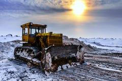 在晚上太阳下的老工业肮脏的黄色拖拉机在多云冬天天空 库存照片