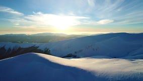 在晚上太阳照亮的多雪的山的飞行 股票录像