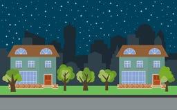 在晚上导航有两个两层动画片房子和绿色树的城市 图库摄影