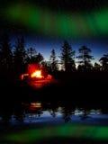在晚上射击燃烧在有北极光的一个森林里 库存图片