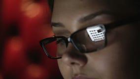 在晚上工作一个少妇的画象戴眼镜的 接近的表面配置文件 股票视频