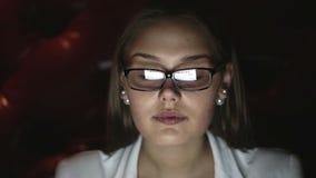 在晚上工作一个少妇的画象戴眼镜的 接近的表面配置文件 股票录像