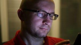 在晚上工作一个年轻人的画象戴眼镜的 关闭 影视素材